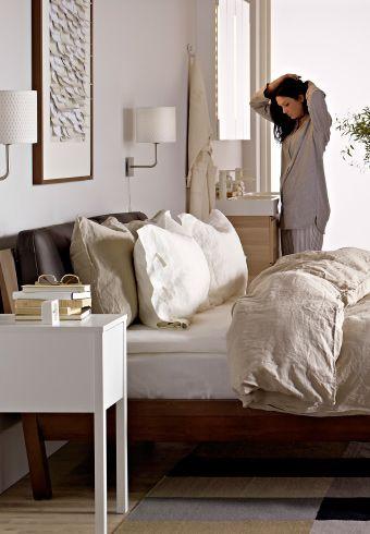 Женщина, стоящая в спальне, обставленной мебелью ИКЕА: кровать, кресло, зеркало, комод и ковер