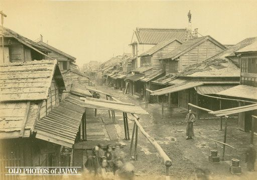 Rackety wooden houses with shingled roofs in Tokyo's Anjincho (安針町) in the Nihonbashi district. This image was published in the June 17 1872 issue of the newsmagazine The Far East, published in Yokohama by the famous Scottish publisher J. R. Black between 1870 and 1878. So we know this photo is at least as old as that date. The area looks dilapidated and squalid, quite different from the views of Japan on the souvenir photos that were soon sold all over the world.