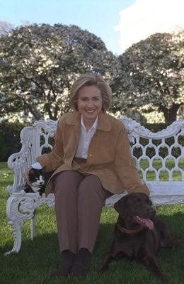 Photograph of First Lady Hillary Rodham Clinton with Socks the cat and Buddy the dog, from the William J. Clinton Presidential Library (photo taken 4/7/1999, photo ID P71379_28A)