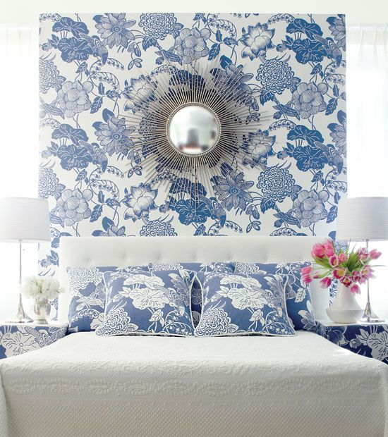 """The wall - papered in the model called """"Cut Paper"""" - gives this quiet bed a magisterial look - especially when combined with matching fabrics for pillows and on tables."""