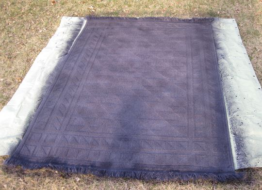 DIY Dyed Rug: de verf oplossen in water en in een plantenspuit sproeien op het tapijt: I had a packet of rit dye that I bought years ago but never used in a blue jean color, but added another packet to make the color deeper. I  dissolved the dye and put it into an empty windex container. Then I sprayed the dye all over the rug. I let it dry, it felt stiff. The next day I totally sprayed the rug, washing out some of the color. This restored the soft feeling of the wool.