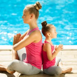 Mother and daughter doing exercise outdoors. Healthy lifestyle. Yoga
