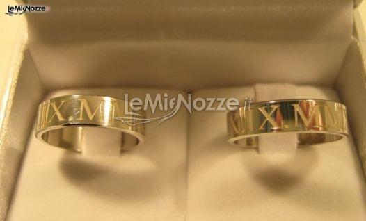 http://www.lemienozze.it/operatori-matrimonio/gioielli/fedi-personalizzate-roma/media/foto/4  Fedi in oro giallo con incisa la data del matrimonio in numeri romani.