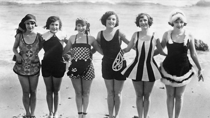 Circa 1929: A row women showing off some unusual and original swimwear on the beach.