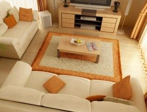 This living room is mostly tan with accents of orange accessories.