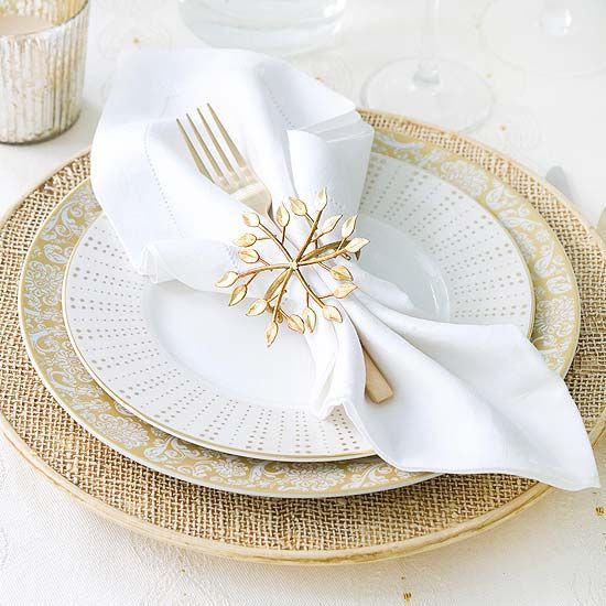 Golden Table Setting: Pull the basics from your china hutch -- white linens, champagne flutes, and your best china -- to create this elegant look. A floral plate and a leafy napkin ring look right for the holidays and year-round. Clear glass cylinders filled with small bundles of flowers create a dainty centerpiece.