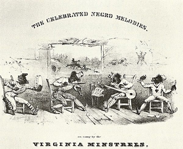 Four-member band in black face make-up playing tambourine, fiddle, banjo and percussion in exaggerated poses.