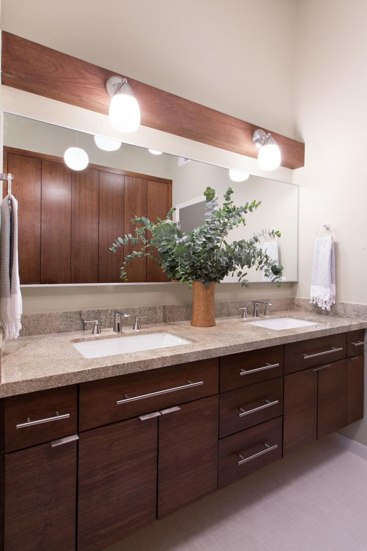 This midcentury modern bathroom was brought back to life with updated light fixtures, a stylish new vanity and custom cabinetry. Thought was given to each finish to ensure the original style of the home was retained with a more modern touch.