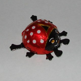"""Chocolate Ladybugs from Germany wrapped in foil with    cardboard legs.  Approximately 1¼"""" in diameter."""
