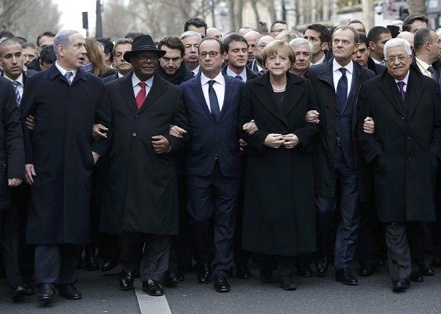 デモ行進に参加し、腕を組んで連帯を示すオランド仏大統領(中央)、メルケル独首相(その右隣)、ネタニヤフ・イスラエル首相(左から2人目)、アッバス・パレスチナ自治政府議長(右端)ら=パリ市内で11日、ロイター