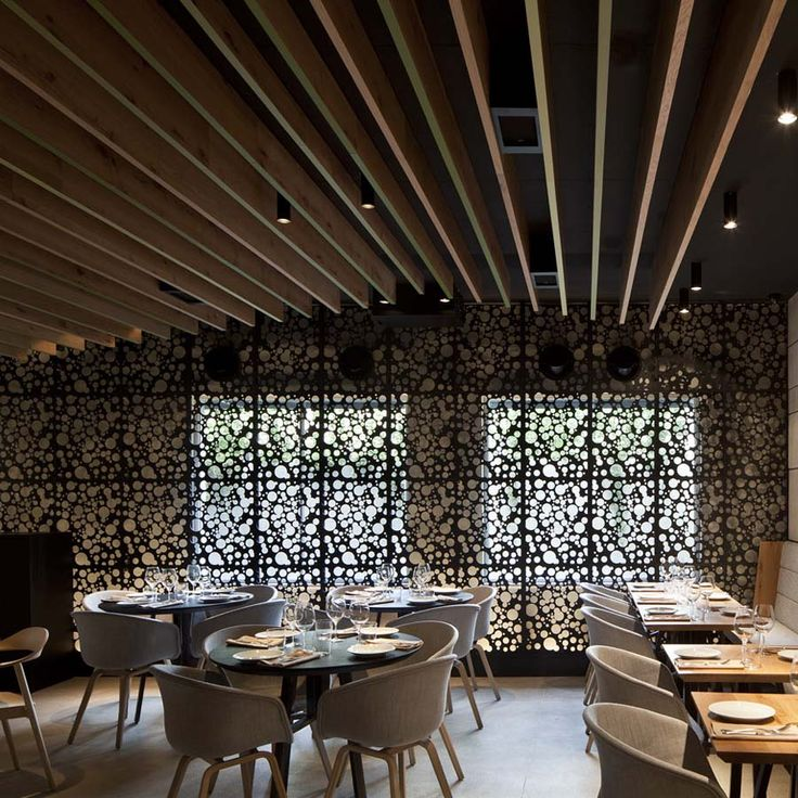 Bindella Osteria & Bar by Pitsou Kedem and Baranowitz-Amit Design Studio in Tel Aviv, Israel The vineyard has been an inspiration for the designers: the ceiling mimics the vineyard's pergola while the grape motif is seen in the metal screens and the feature front door.