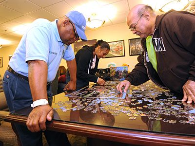 """Herbert """"The Puzzle Man"""" Brown has worked 25 different jobs, but now is spending his retirement as a volunteer at the Cancer Treatment Centers of America facility in Philadelphia. His daily routine ranges from greeting patients with a hug and asking about their day, to talking about serious issues and staying with them in intensive care. But he is most known for his jigsaw puzzles. (Story by Gillian Francella / Philly.com)"""