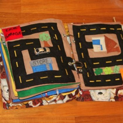 Like roadway idea for travel.  Could do whole quiet book with roads, helicopter landings, airport runways, carriers, dirt tracks, railroad, etc... To play with his small cars, planes, motorcycles, trains. Maybe have page with pockets in the front for keeping the vehicles with the book for travel.