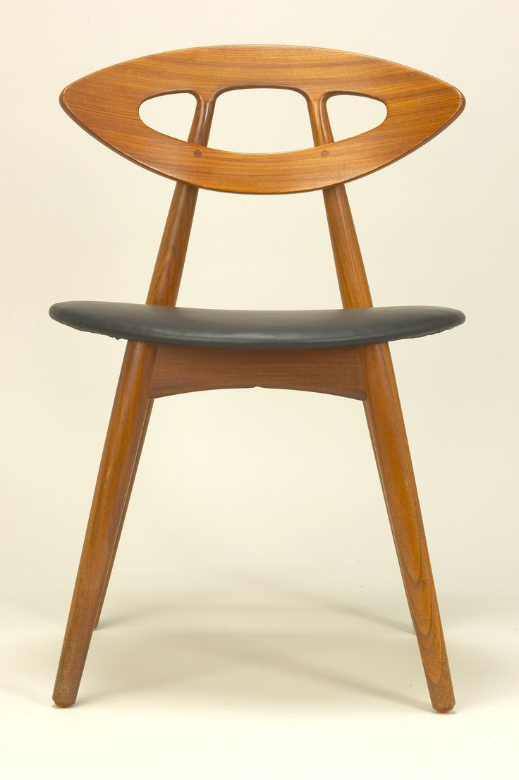 Designed by Ejvind A Johansson Denmark    Circa 1960    Manufactured by Ivan Gern Furniture Denmark  Teak dining chairs have eye shaped backs and upholstered in black leather.