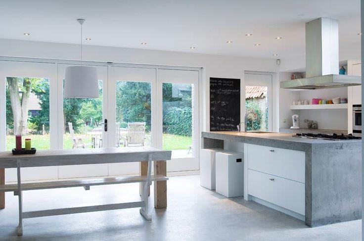reforma cocina con muebles e isla central de obra con barra y suelo con acabado microcemento.