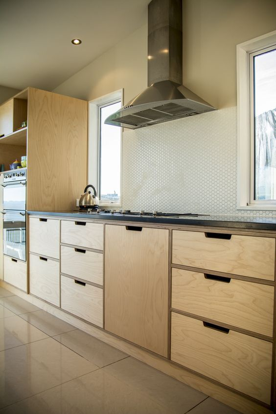 Crisp, simple and modern plywood kitchen. Oiled Birch plywood and absolute black honed granite. Lots of clever storage and a dream to work in.: