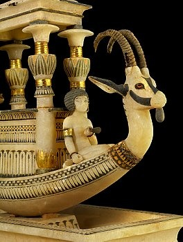 Detail of alabaster boat model with ibexes from tomb of Tutankhamun  In the middle of the tank is a support on which rests a boat adorned on prow and stern with ibex heads with real horns and pierced ears. The boat is occupied by a shrine in front of which is a servant girl holding a lotus. At the stern a female dwarf stands holding a sounding pole. Both are symbols of solar rebirth. | Located in: Egyptian Museum, Cairo.