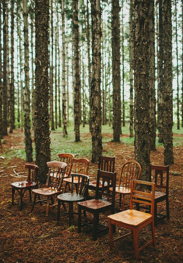This vintage setup is beautiful using simple missmatched chairs in a woodland setting