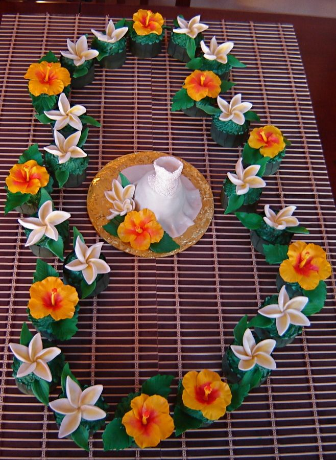 For a bridal shower of a bride to be married in Hawaii.  Each flower is an individual cupcake.  Hibiscus and plumeria are gumpaste, skirt of gown is fondant, gown bodice is gumpaste covered in white non-perils.  Home made cuppie covers.