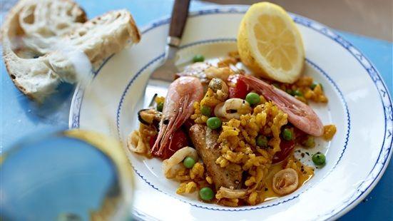 Tina skaldjuren och låt rinna av i ett durkslag. Skär kycklinglårfiléerna i tre delar och bryn i olivoljai en paellapanna eller en stor traktörpanna, ca 3 minuter. Krydda med salt och peppar. Tillsätt lök, vitlök, paprika, paprikapulver och saffran. fräs ytterligare 3 minuter. Tillsätt sedan ris, tomater,vatten och fond. Låt koka upp under lock och låt sedan småputtra 20 minuter under lock tills riset är genomkokt. Vänd ner skaldjursmixen i paellan. Lägg räkor och ärtor på toppen och lägg på…