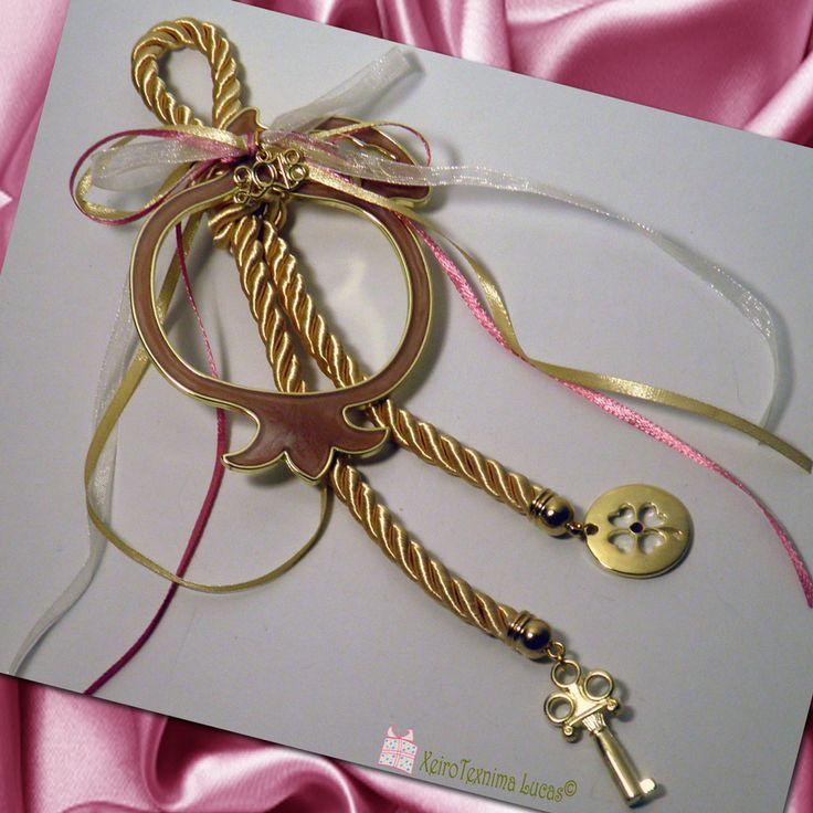 Ελληνικό χειροποίητο γούρι 2018. Αποτελείται από ένα μεγάλου μεγέθους ρόδι (περίγραμμα) σε χρυσό χρώμα με ροζ σμάλτο δεμένο σε χρυσό στριφτό γυαλιστερό κορδόνι με σατέν κορδέλες διακοσμημένο με μεταλλικά στοιχεία. Metal pomegranate with rose enamel decorated with a gold cord, satin ribbons a key and a fourleaf as a good luck charm for 2018. A great gift for a happy new year.