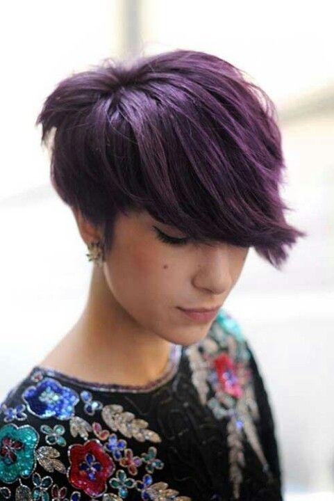 Sur cette photo, l'asymétrie se joue sur les longueurs de l'avant et de l'arrière. On peut voir que la nuque a été rasée, mais que le dessus de la tête est assez long. Et pour augmenter le volume, le coiffeur de cette jeune femme a ramené ses cheveux vers l'avant tout en y dessinant une jolie pointe sur le front. Les mèches violettes ajoutent de la lumière à la coloration noire.