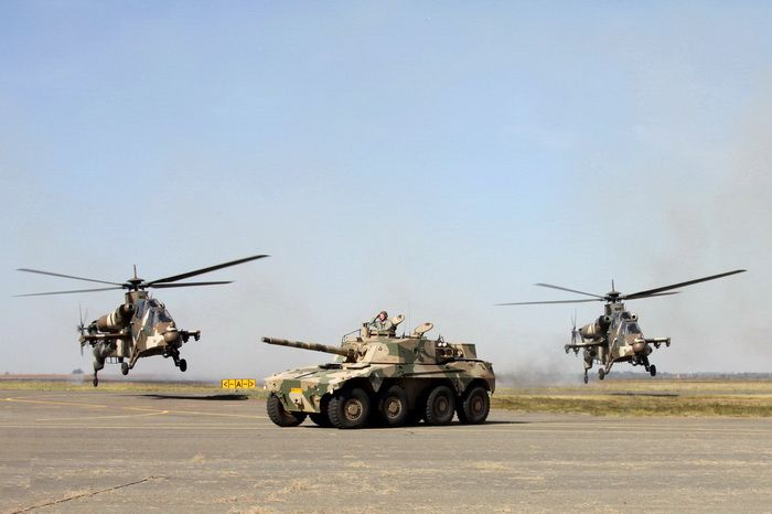 Rooikat armoured vehicle flanked by two Rooivalk attack helicopters.