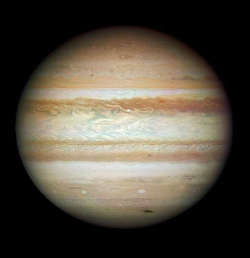 Image de Jupiter avec ses couleurs naturelles. La tache sombre en bas à droite sur la planète est formée des débris d'une comète ou d'un astéroïde qui s'y est écrasé.