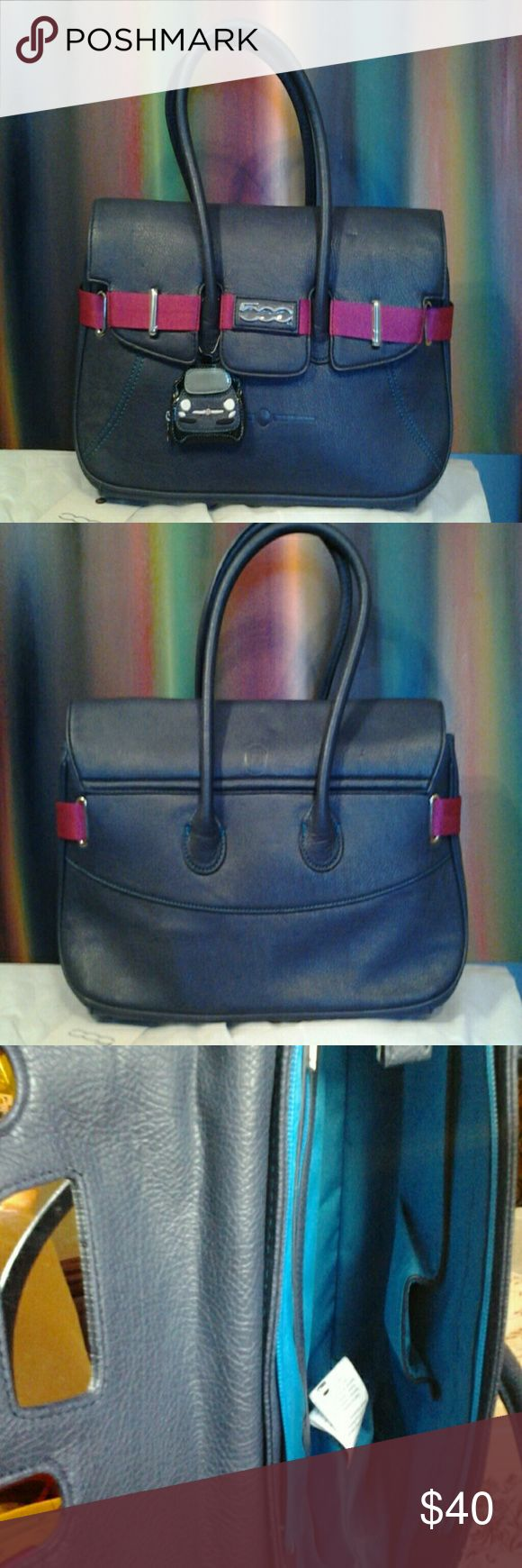 "Fiat 500 Chic Bi-color Handbag Large Navy faux leather w/ dark pink nylon contrasting strap design, quality teal stitching. Main zipper closure, top flap has three exterior magnetic closure . Teal interior w/ zipper closure pocket @ back, & two open cellphone pockets @ interior front.mirror @ interior of flap.  Silver hardware, removable fiat change purse hangs @ exterior handle. Some very minor marks on leather. Interior pristine, never used. Comes with duster bag, marks on duster bag. 18""w…"