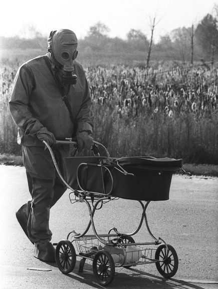 A liquidator pushes a baby in a carriage who was found during the cleanup of the Chernobyl nuclear accident. The infant had been left in an abandoned house in the village of Tatsenki; the worker found the child when he was measuring radiation levels.    Chernobyl, Ukraine, 1986