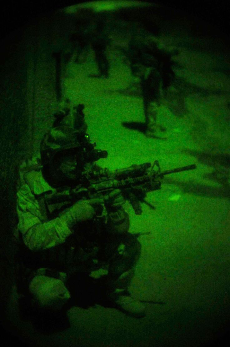 Army Special Forces soldier, wearing night vision goggles, provides cover for a joint US Special Forces - Iraqi Special Operations Forces night raid.
