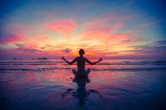Woman doing meditation near the ocean beach. stock photo