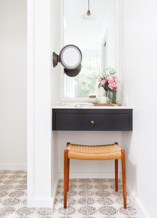 Gorgeous vanity nook features a black floating dressing table with white mirror above, and wall mount make-up mirror to the right, over a mid-century modern teak vanity stool atop hand painted terracotta floor tiles.