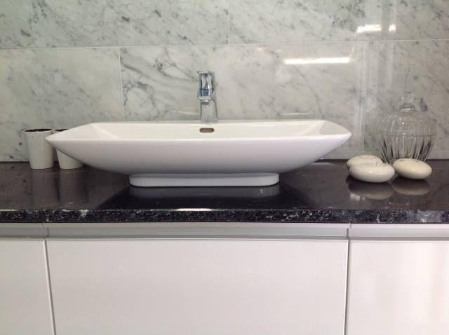 Yläkerran makuuhuoneen kylppärissä on seinässä Tulikiven Bianco Carrara -marmoria. Taso on Stormy Black -mustaa graniittia. Kohde: Kiven Herra.