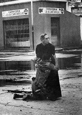 Braving the streets amid sniper fire to offer last rites to the dying, the priest Luis Padillo encountered a wounded soldier, who pulled himself up by clinging to the priest's cassock, as bullets chewed up the concrete around them. The last rites are the last prayers and ministrations meant to prepare the dying person's soul for death. (This photo won the World Press Photo of the Year in 1962)