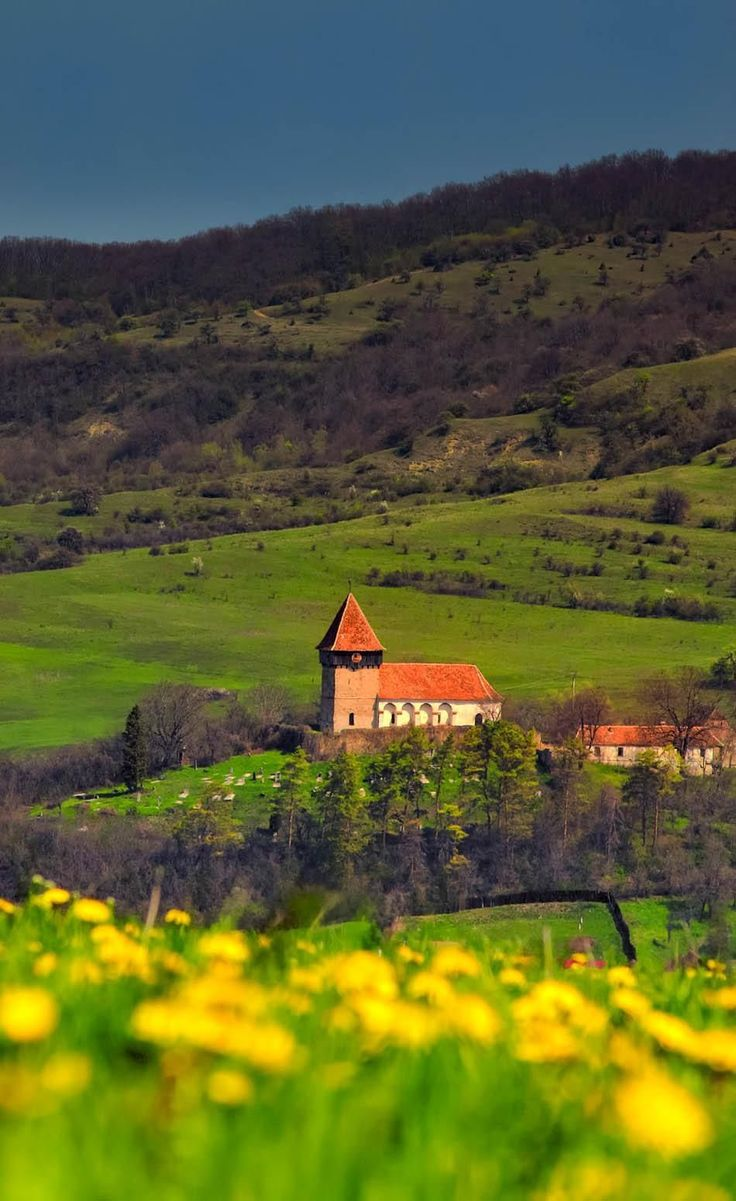 Overcast Landscape over the Transylvanian village of Rodbav with the church on the hill, Romania. | Discover Amazing Romania through 44 Spectacular Photos