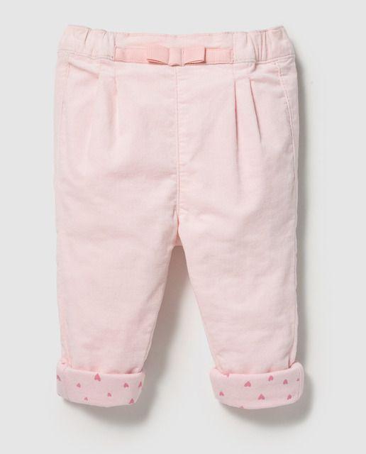 Pantalón con pinzas en color rosa, con cintura elástica. Tiene detalle de lazo a tono en delantero.