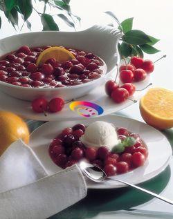 [Ciliegie caramellate] Snocciolate le ciliege. In una padella mettete del burro, lo zucchero e cuocete fino a quando lo zucchero si è caramellato.     Unite le ciliege e mescolate per qualche minuto poi versate il succo di arancia ed il kirsch.     Cuocete per alcuni minuti poi versate il tutto sopra al gelato in quattro ciotole individuali. Servite subito.