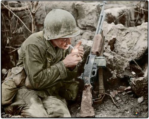Pfc. Terry Paul Moore of Albuquerque, New Mexico. He was number one Browning Automatic Rifleman in 2nd Platoon, Company 'F', 184th Infantry Regiment of the US 7th Infantry Division and is lighting his first cigarette of the day on the island of...