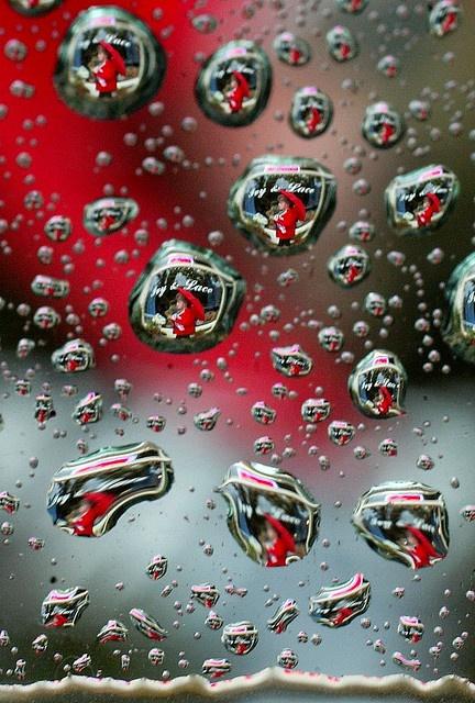 A pedestrian is seen through the myraid pattern in tiny raindrops on a car window.  John Walker/Fresno Bee