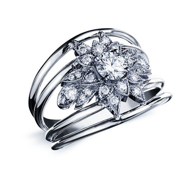 PRISCILLIA : Bague en or blanc constituée de quatre anneau soutenant un diamant rond au centre entouré de plus petits diamants en forme de pétales de fleur #bague #orblanc #diamants #bijoux #luxe #valeriedanenberg #fleur