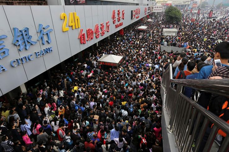 """Passengers wait to get into the crowded Zhengzhou Railway Station on the first day of """"the Golden Week,"""" a holiday that celebrates the founding of the People's Republic of China."""