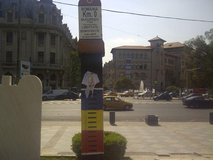 """LACOTEC en la Plaza de la Universidad (Bucarest, Rumanía): El """"kilómetro cero"""" de Rumanía está marcado por un monumento localizado enfrente de la iglesia de San Jorge en el centro de Bucarest. Curiosamente existe otro """"kilómetro cero"""" en Bucarest, en esta ocasión de carácter simbólico-político anticomunista; enfrente del Teatro Nacional (en la Piaţa Universităţii), se haya este pequeño monolito levantado tras el levantamiento contra el Régimen de Caucescu en 1989."""