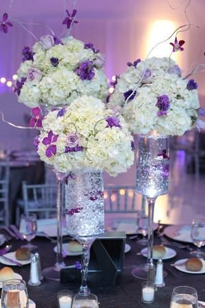 To compliment the lavender ambiance of the venue, the couple chose a whimsical combination of white hydrangea, purple dendrobium orchids and lavender roses for their guest tables.  Venue: Miami Tower. Flowers by Lush Celebrations, Miami, FL