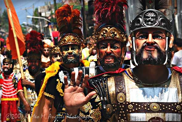"""The MORIONES is an annual festival held on Holy Week on the island of Marinduque, Philippines. The """"Moriones"""" are men and women in costumes and masks replicating the garb of biblical Roman soldiers as interpreted by local folks – Morion means """"mask"""" or """"visor,"""" a part of the medieval Roman armor which covers the face. The Moriones or Moryonan tradition has inspired the creation of other festivals in the Philippines where cultural practices or folk history is turned into street festivals."""