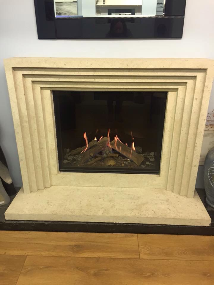 The Bellfire Derby Large 3, Hidden Door, Log Effect gas fire set in a Wessex Stone 'Helmsley' fireplace in base limestone.