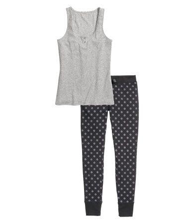 Een tweedelige pyjama van zacht tricot van katoenmix. De singlet is van geribd tricot en heeft een knoopsluiting boven en een kanten biesje langs de halsopening. De broek heeft elastiek en een drawstring in de taille en een brede boord onder aan de pijpen.