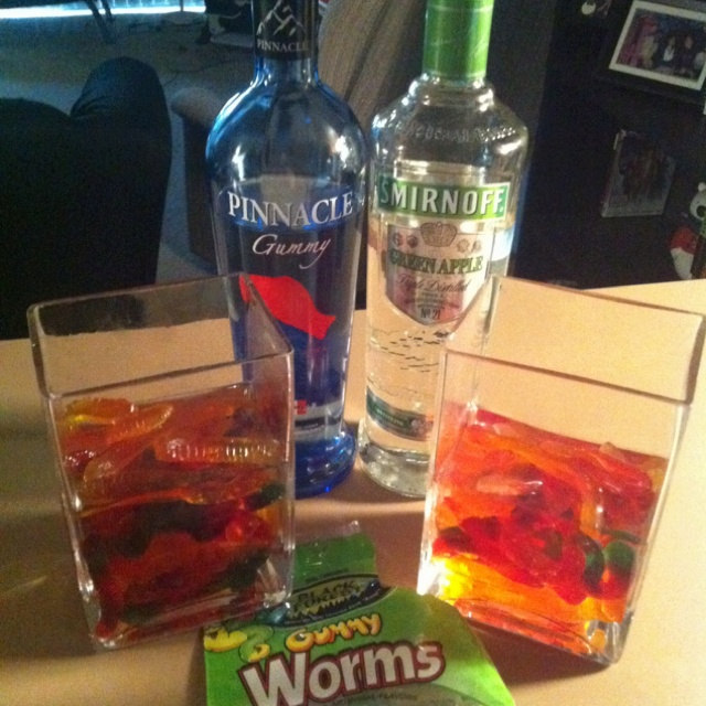 Alcoholic Gummy Worms! 1. Pour gummy worms in a glass container. 2. Pour vodka until it covers the worms (We used Smirnoff green apple vodka and Pinnacle gummy vodka). 3. Put them in the fridge and let them soak until the vodka has been absorbed.