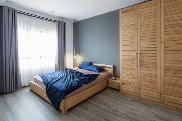 Apartment: Interesting ML Apartment in Hanoi, Vietnam Designed by Le Studio, ML Apartment Master Bedroom Idea by Le Studio showing Wooden Bed Frame and Blue Comforter and Mini Bedside Table also Huge Cupboard and Laminate Wood Flooring