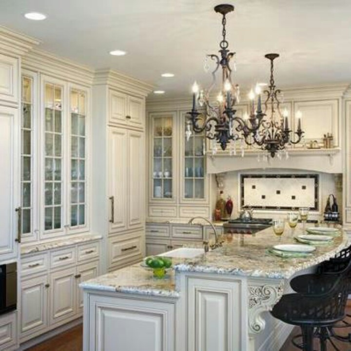Traditional kitchen by drury design kitchen bath studio elegant with chandeliers and glass cabinetry